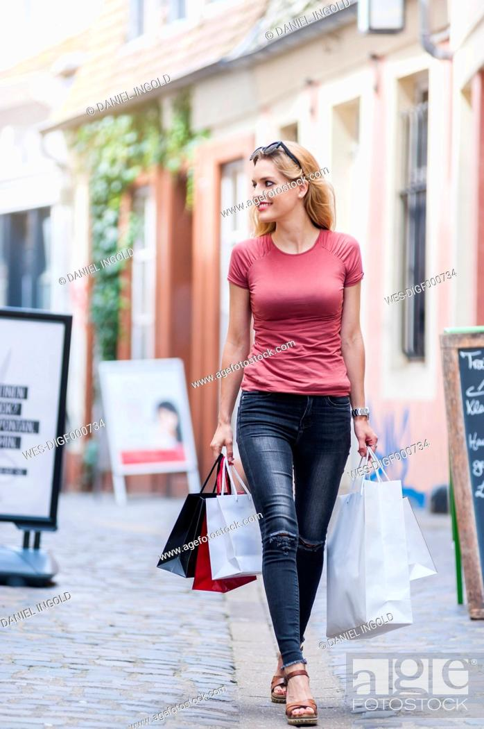 Photo de stock: Smiling woman walking on the street carrying shopping bags.