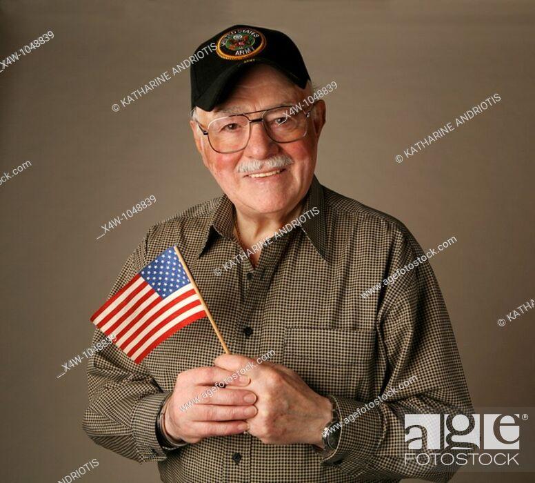 Stock Photo: An proud American senior World War II veteran holding flag.