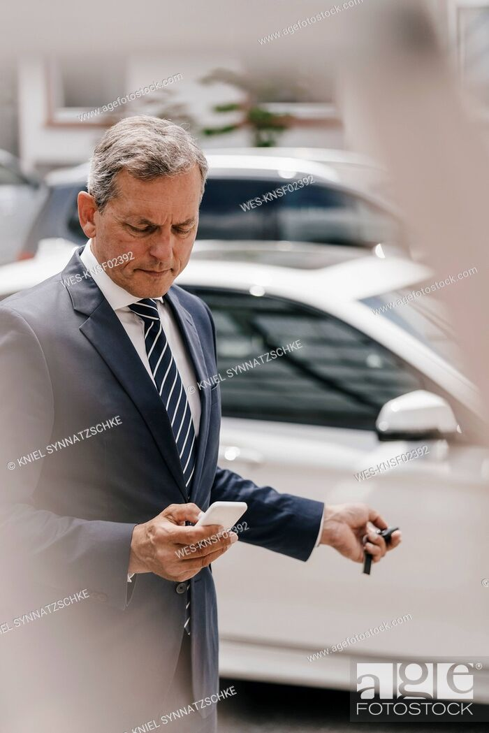 Stock Photo: Businessman checking message while using remote control key of car.