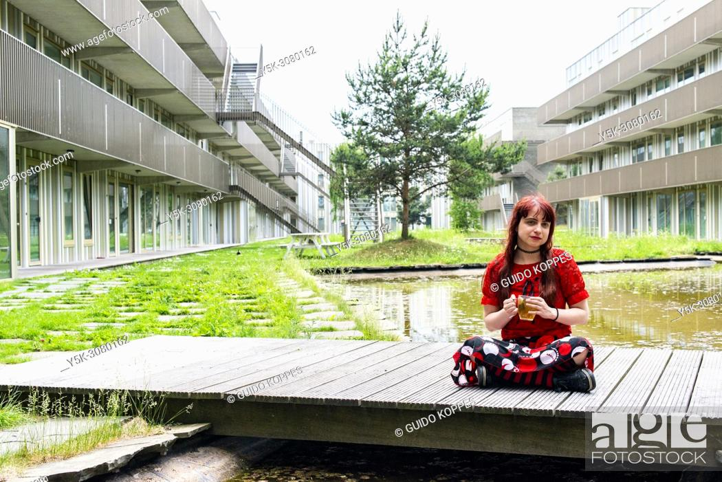 Photo de stock: Amsterdam, Netherlands. Young, redhaired woman sitting realy Zen on a closed garden bridge inside her apartment building, while drinking a hot cup of tea.