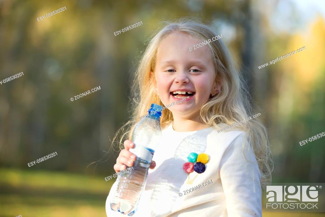 Stock Photo: Joyful little girl child blonde drinks water from a bottle.