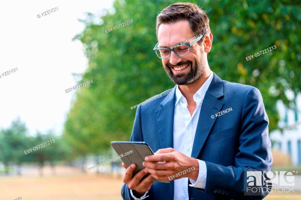 Stock Photo: Smiling businessman wearing eyeglasses using digital tablet in the park.