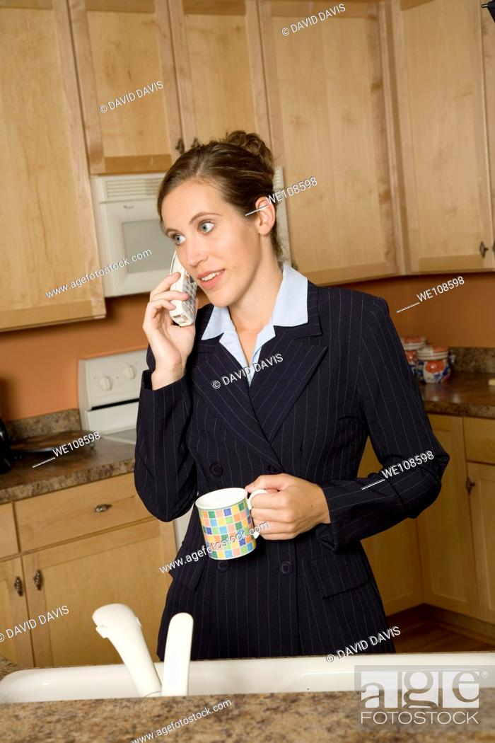 Stock Photo: Businesswoman in early 20s standing in the kitchen dresses in a business suit and holding a coffee cup and talking on the telephone.