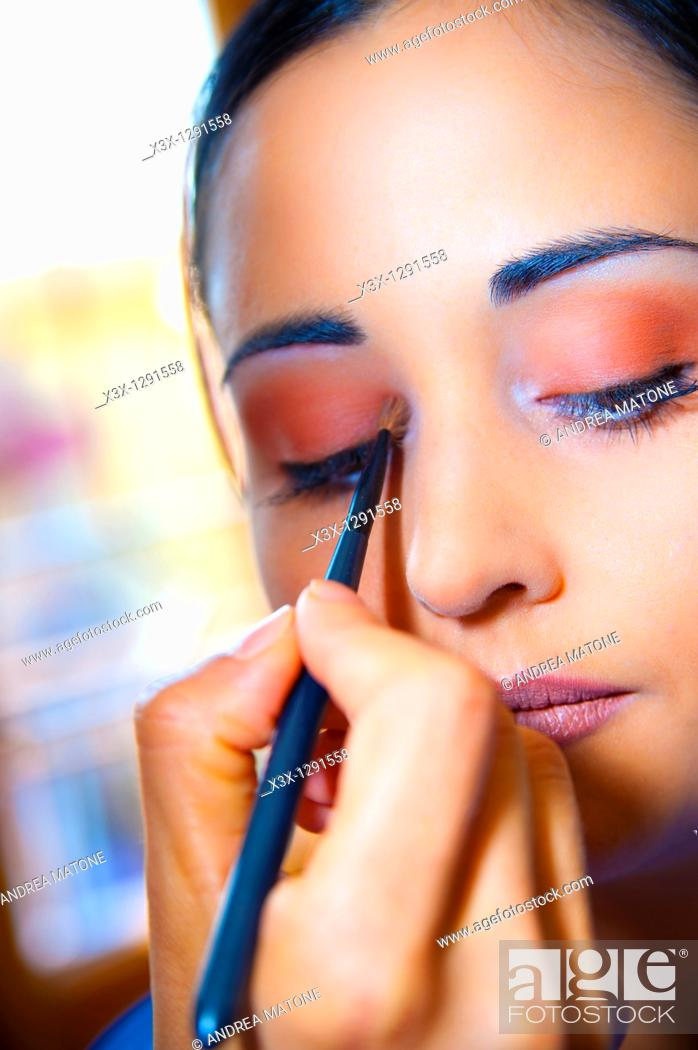 Stock Photo: Woman applying eye shadow during make up session.