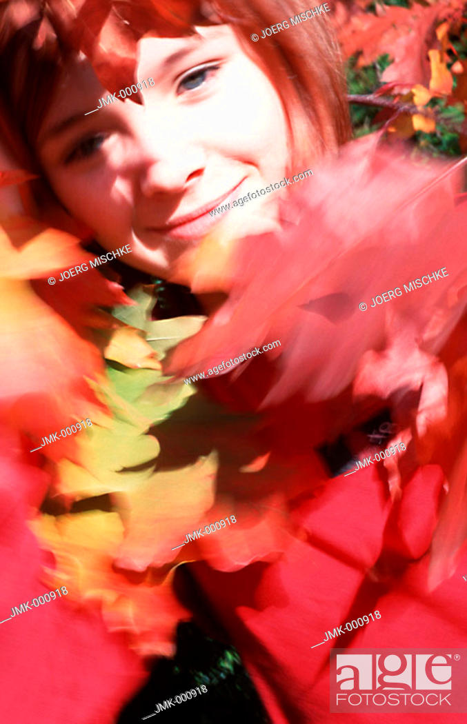 Stock Photo: Little girl in the garden behind coloured leaves.