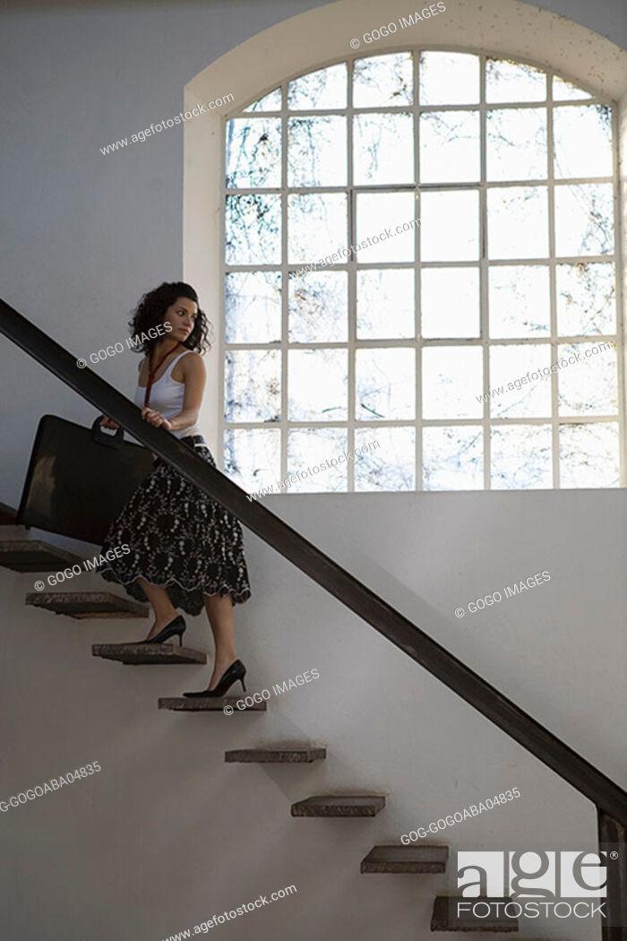 Stock Photo: Woman climbing a staircase.