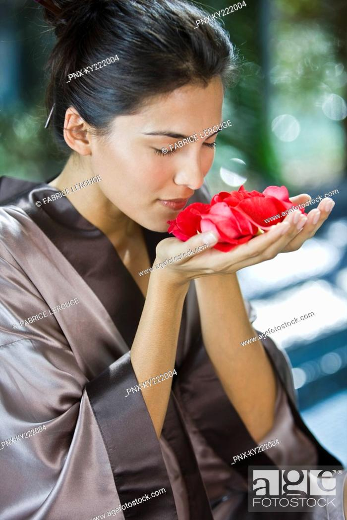 Stock Photo: Woman smelling rose flowers.