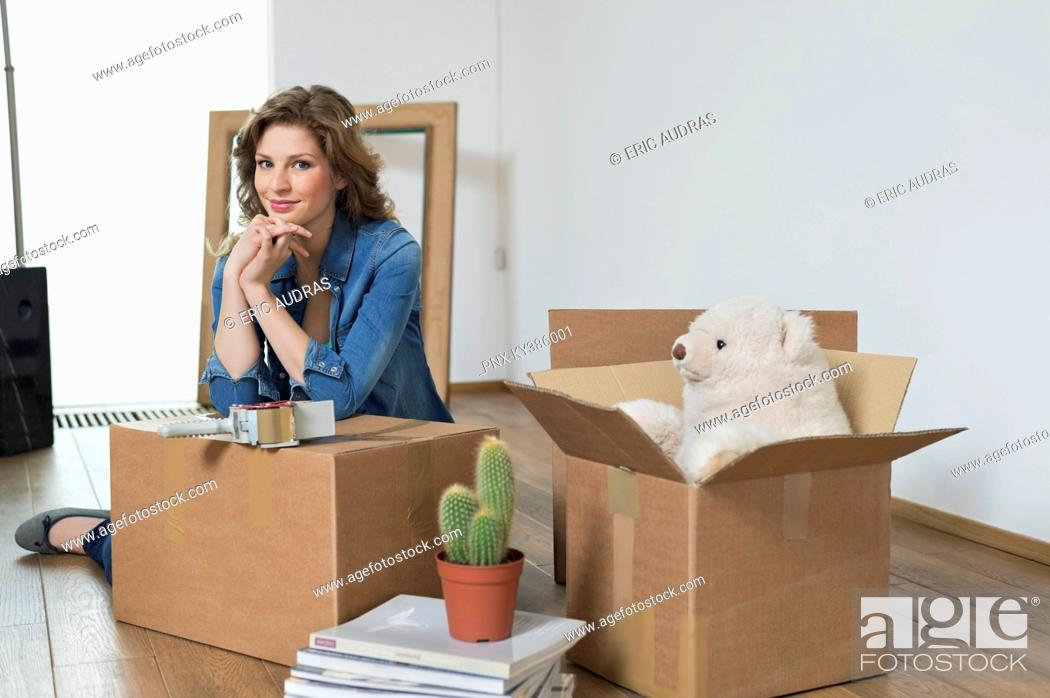 Stock Photo: Woman leaning on a cardboard box and smiling.