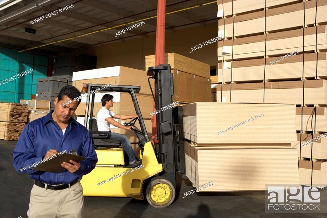 Stock Photo: Man with clipboard in front of forklift stacking boxes.
