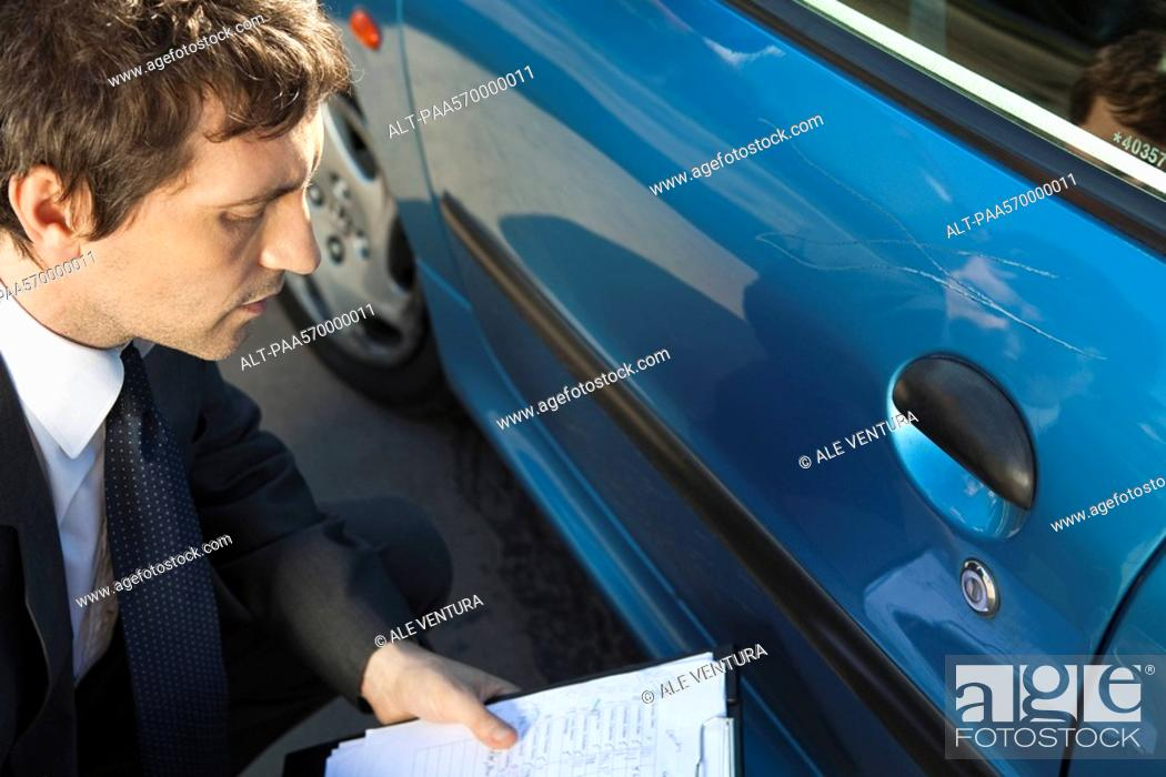Stock Photo: Insurance adjuster examining damage to car exterior.