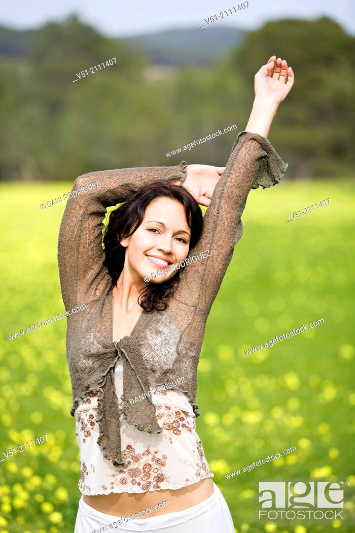 Stock Photo: Brunette pretty woman in park smiling at camera.