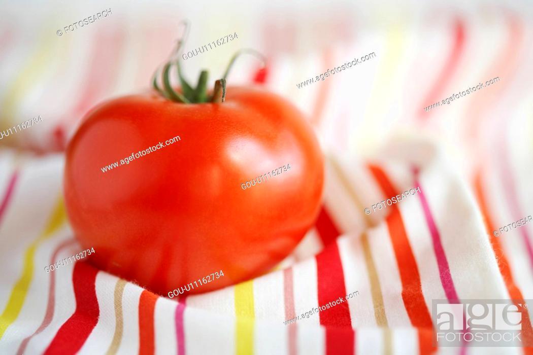 Stock Photo: Single tomato on stripy tablecloth.