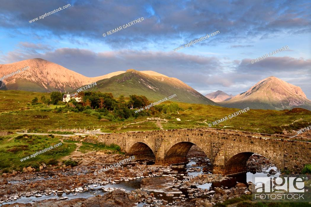 Stock Photo: Sligachan Old stone Bridge over River Sligachan with Beinn Dearg Mhor and Marsco peak of Red Cuillin mountains at sunset Isle of Skye Scotland UK.