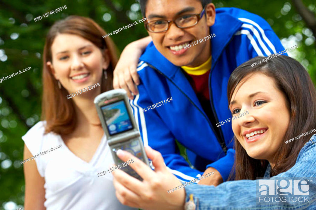 Stock Photo: Close-up of three college students taking their picture with a mobile phone.
