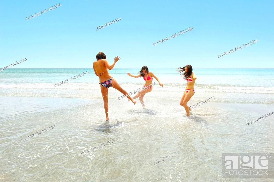 Stock Photo: Three girls splashing each other.