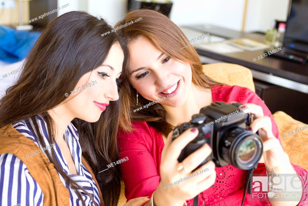 Photo de stock: Two young women with their camera on the couch of their house in the morning.