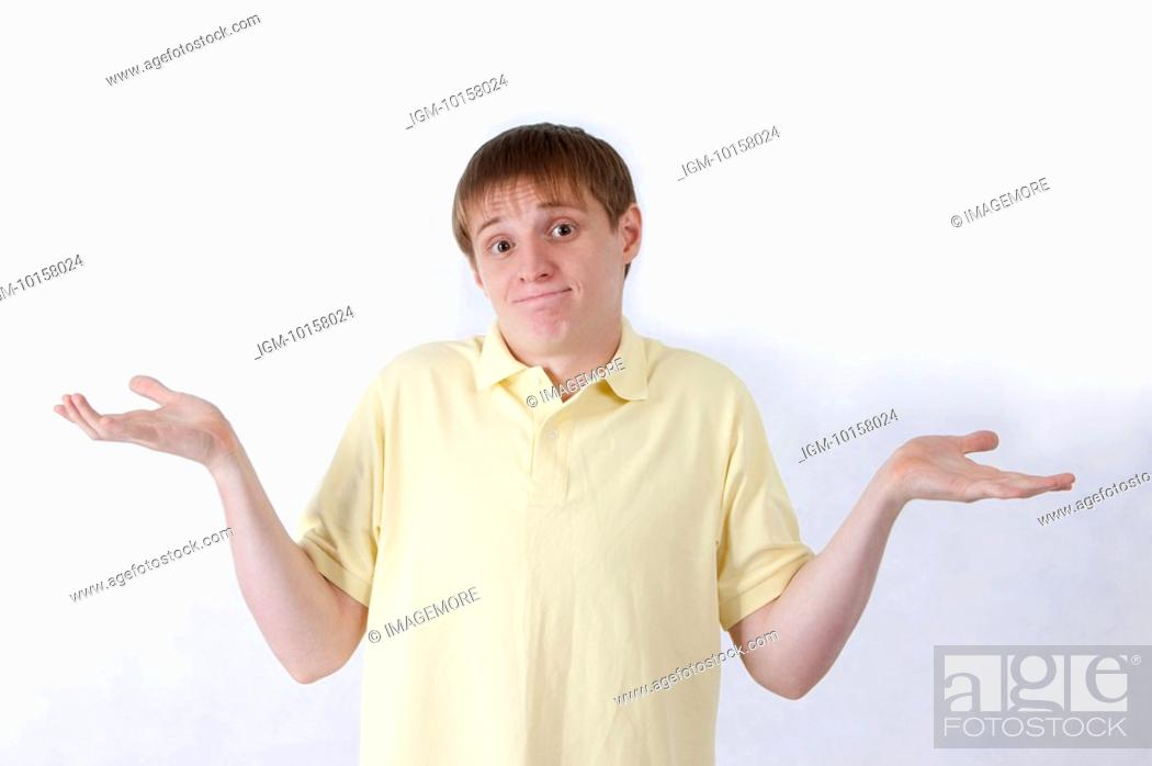 Stock Photo: Young man shrugging and looking at the camera with helpless gesture.