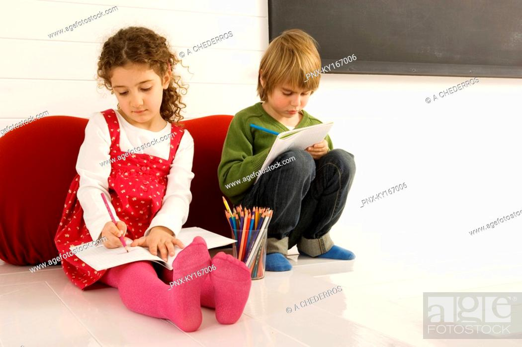 Stock Photo: Boy and a girl drawing on notepads.