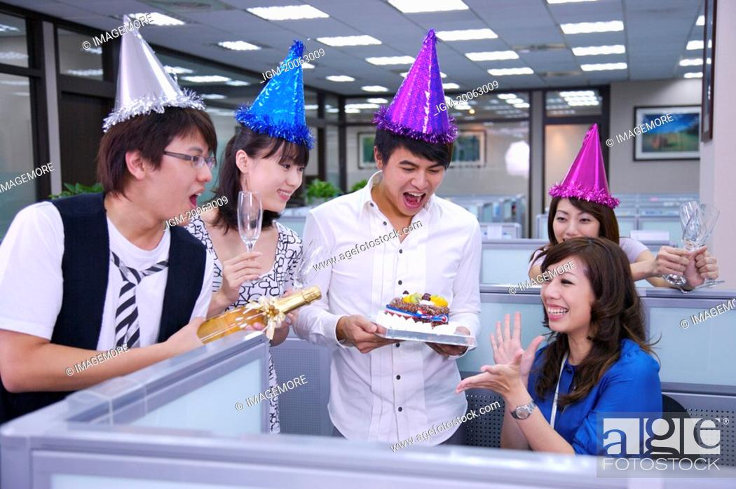 Stock Photo: Colleagues wearing headwear and holding a cake for celebrating.