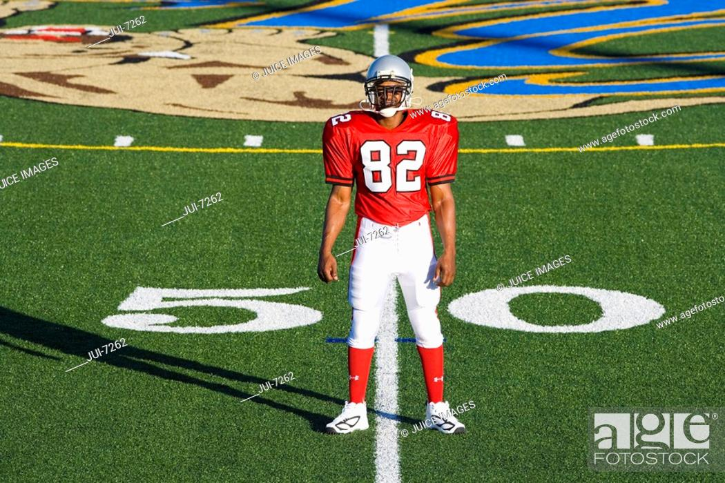 Stock Photo: American football player, in red football strip and protective helmet, standing on pitch at 50 yard line, front view, portrait.