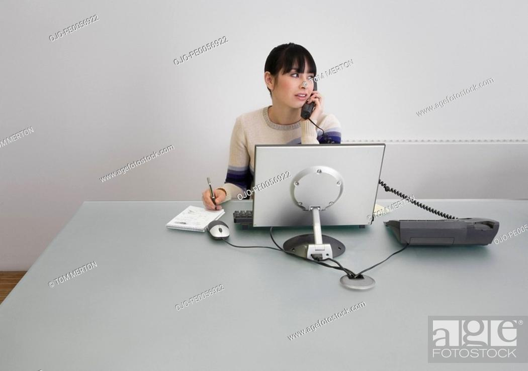 Stock Photo: Businesswoman on telephone in an office.