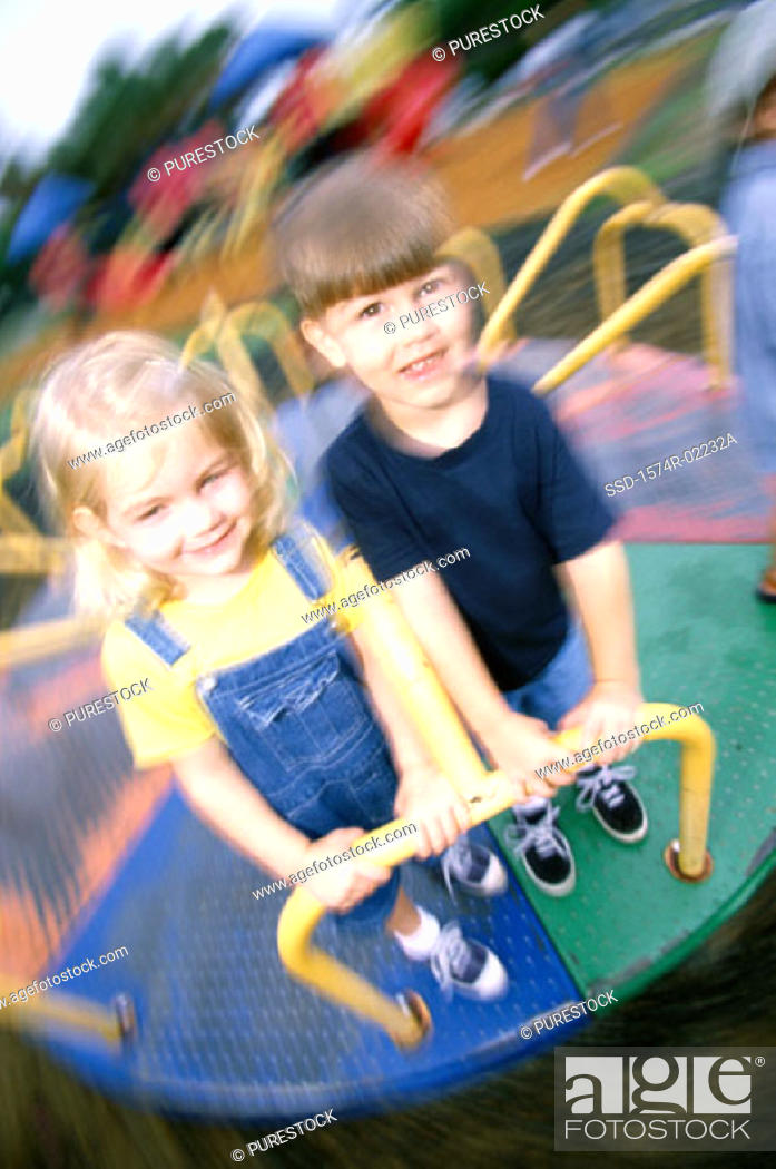 Stock Photo: Portrait of a boy and a girl standing on a merry-go-round.