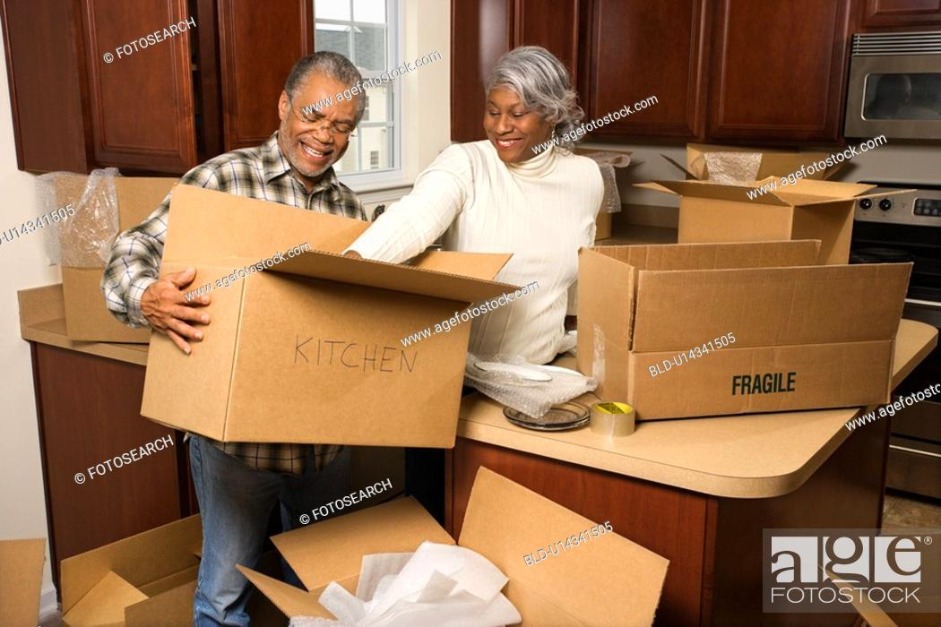 Stock Photo: Couple packing moving boxes in kitchen.
