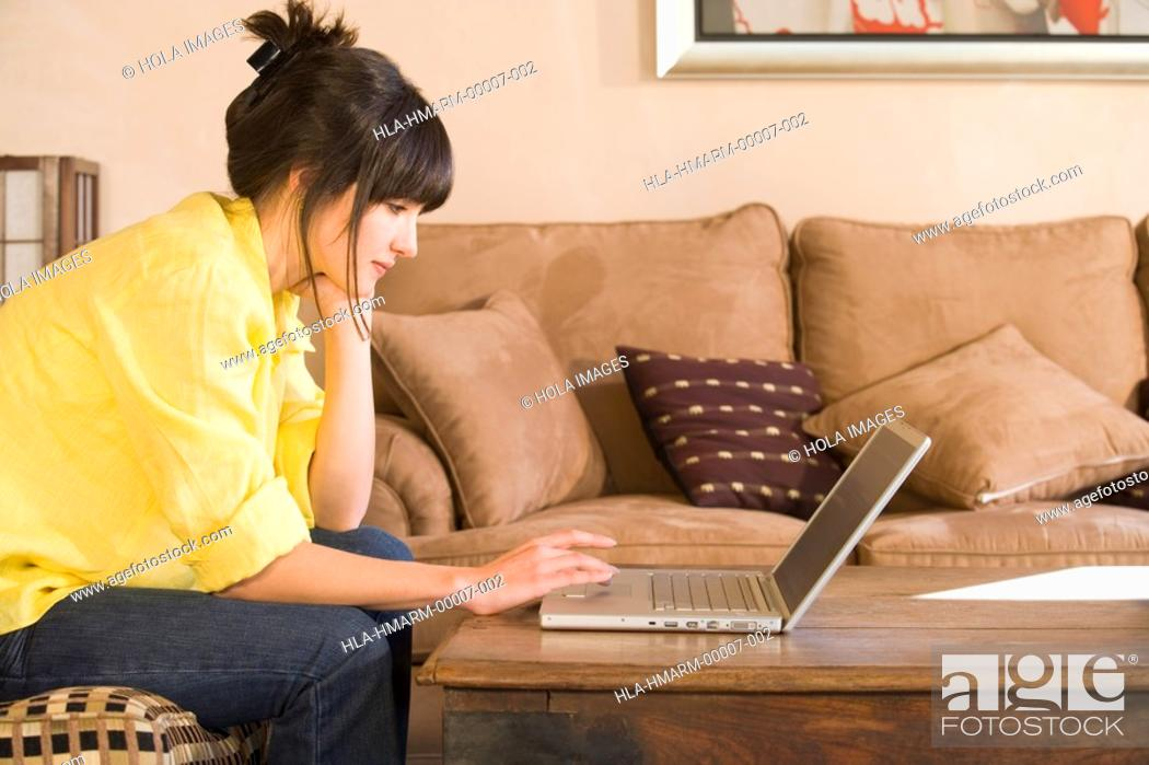 Stock Photo: Woman working on laptop in living room.