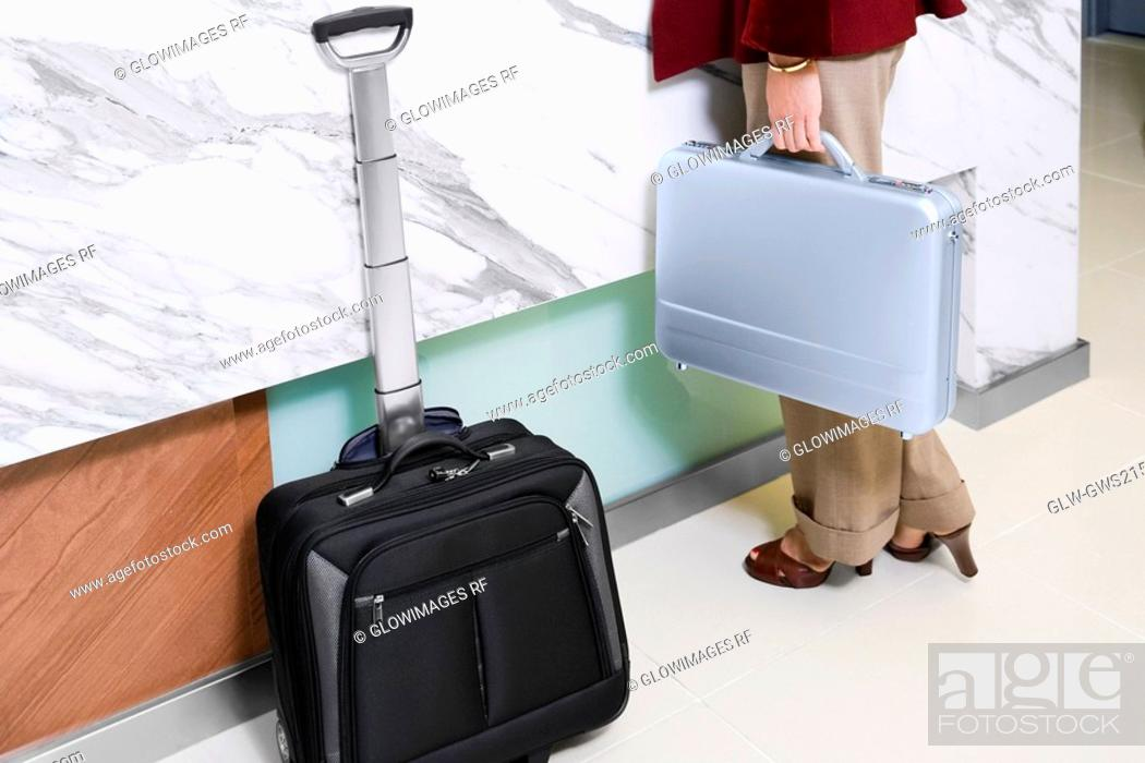 Stock Photo: Low section view of a woman holding a briefcase.