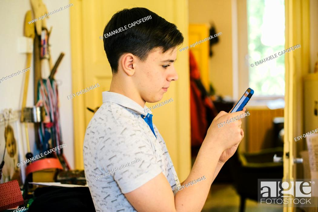 Stock Photo: teen boy looks at the smartphone in his home- portrait of boy reading on the smartphone.
