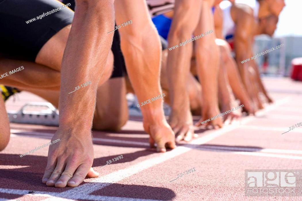 Stock Photo: Male sprinters on starting blocks, low section.