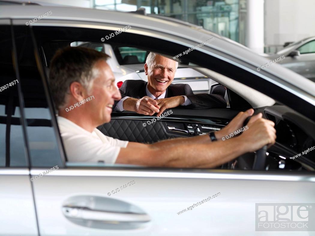 Stock Photo: Salesman talking to man in new car in showroom.