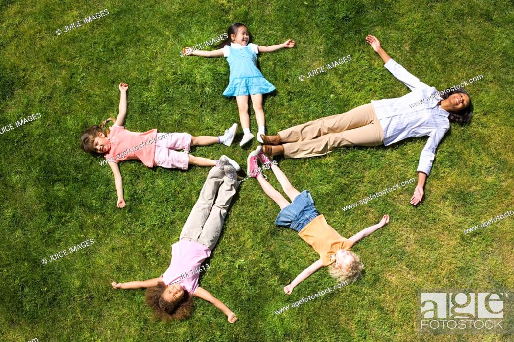 Stock Photo: Woman with girls 4-8 lying on grass making star shape.