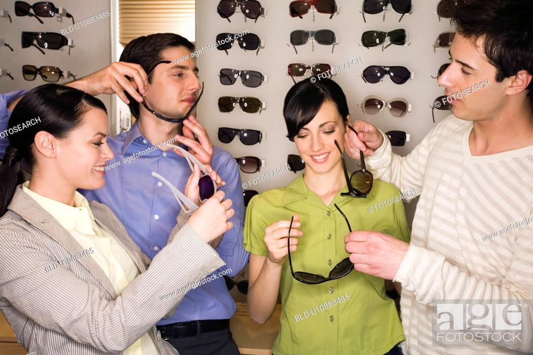 Stock Photo: Two couples shopping for sunglasses in store.