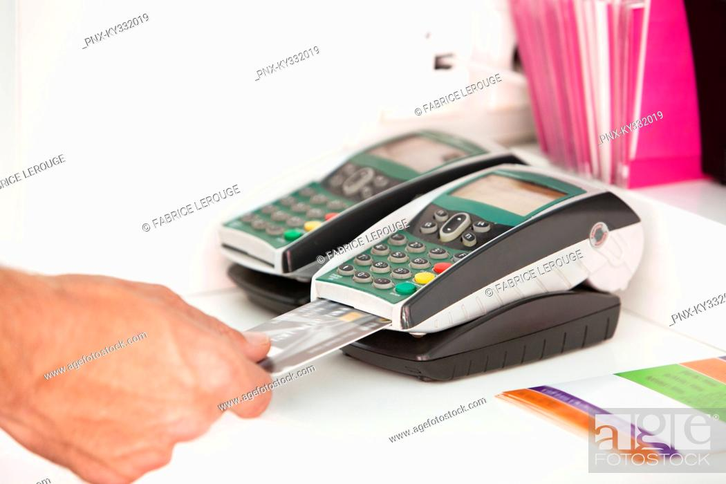 Stock Photo: Sales clerk inserting a credit card in a credit card reader.