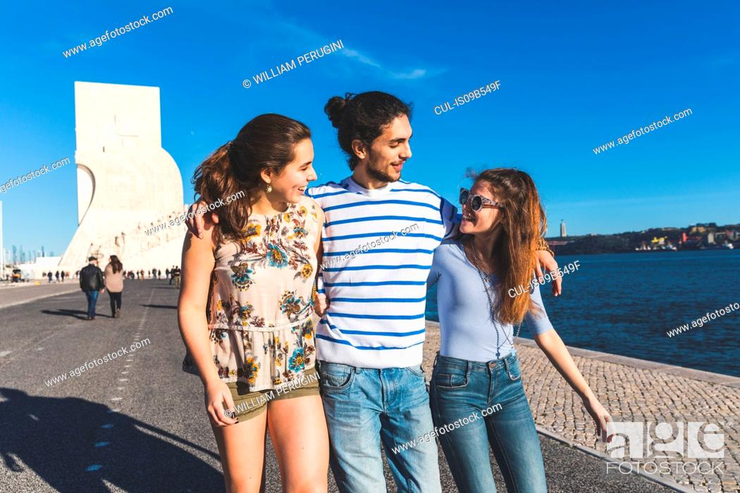 Stock Photo: Three friends, walking by sea, Monument to the Discoveries in background, Lisbon, Portugal.