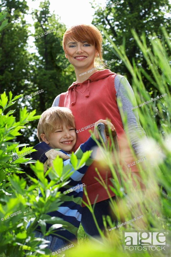Stock Photo: Mother embracing son 5-6 in garden portrait.
