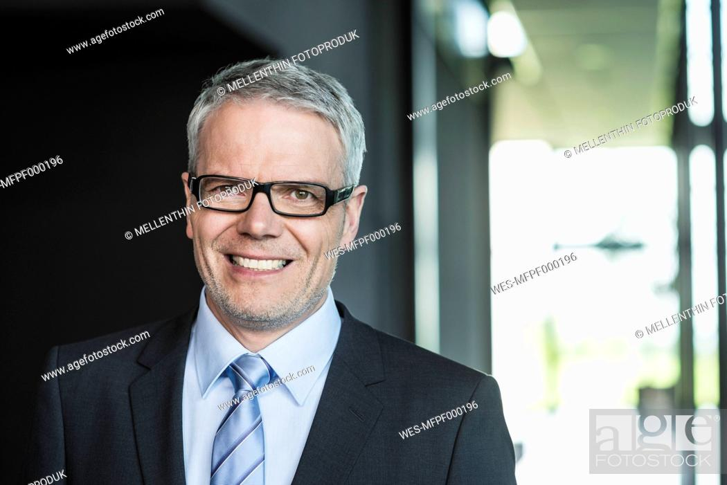 Stock Photo: Germany, Stuttgart, Businessman standing in office building, smiling.