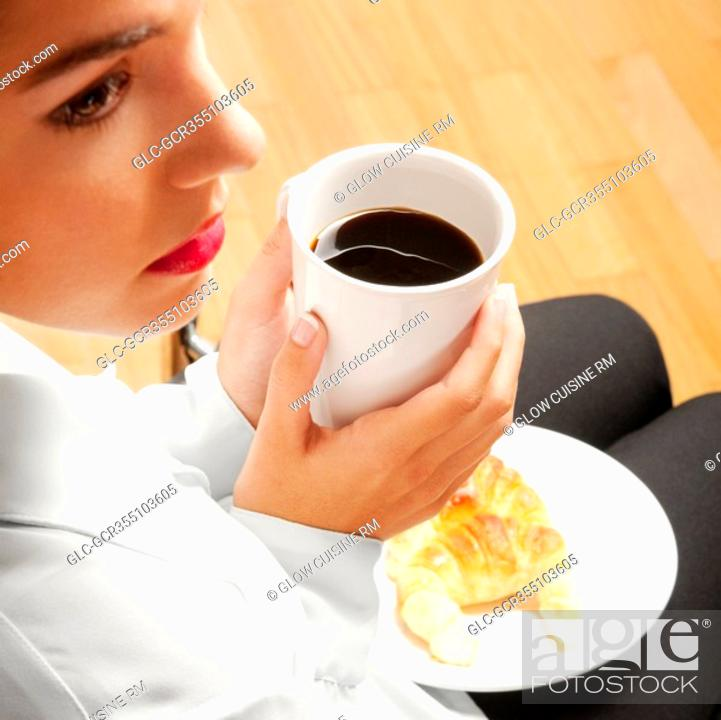 Stock Photo: Woman sitting with a cup of coffee and plate of croissants.