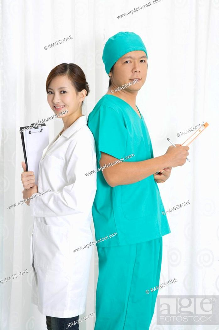 Stock Photo: Female doctor and surgeon standing with back to back and looking at the camera.
