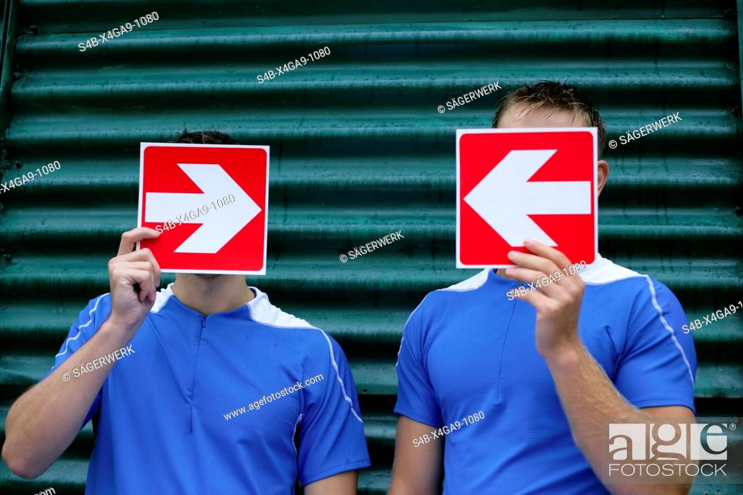 Stock Photo: Two men holding arrow signboards in front of the face.