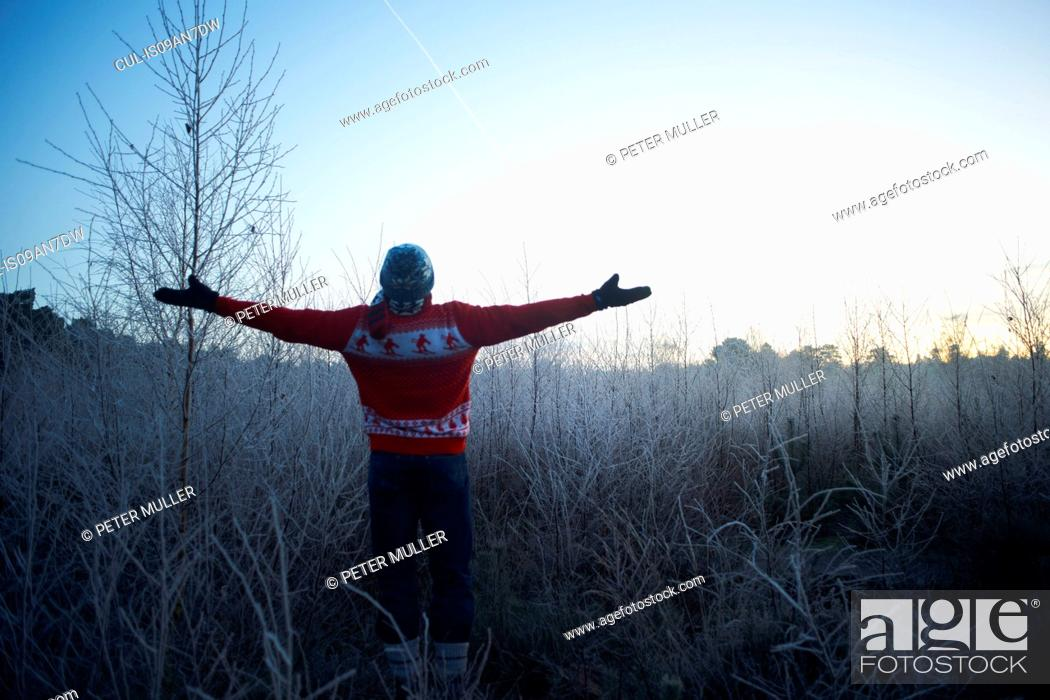 Stock Photo: Man with arms open in sunlit rural winter scene.