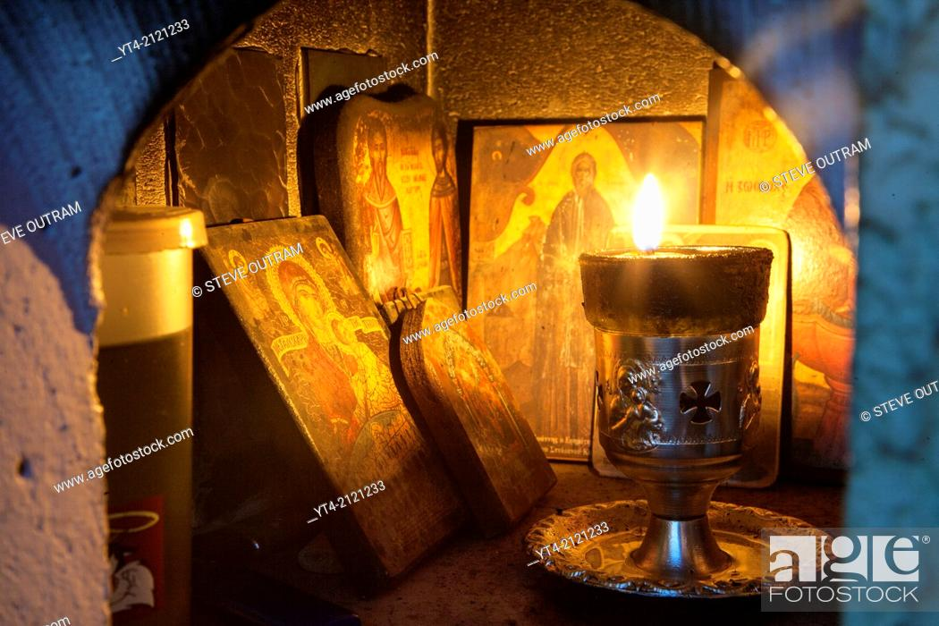 Stock Photo: A lit candle and Icons inside a Religious Shrine ( Eklisaki ) Crete, Greece.