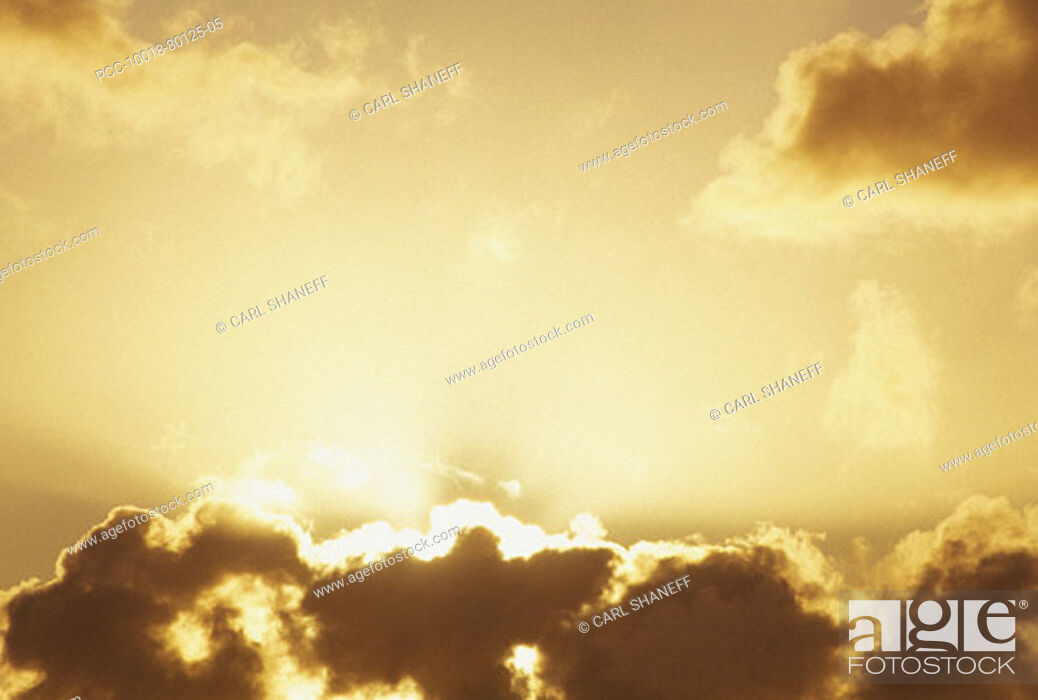 Stock Photo: Bright sun shining behind the clouds in yellow sunset sky.