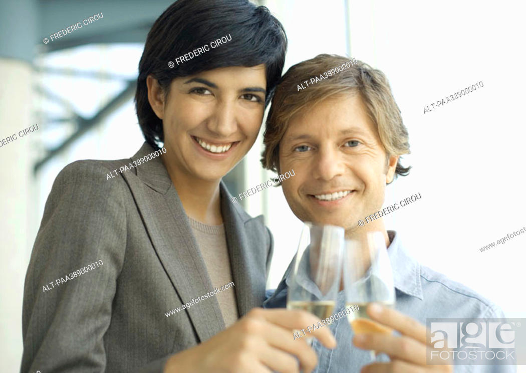 Stock Photo: Professional man and woman clinking glasses of champagne, smiling at camera.