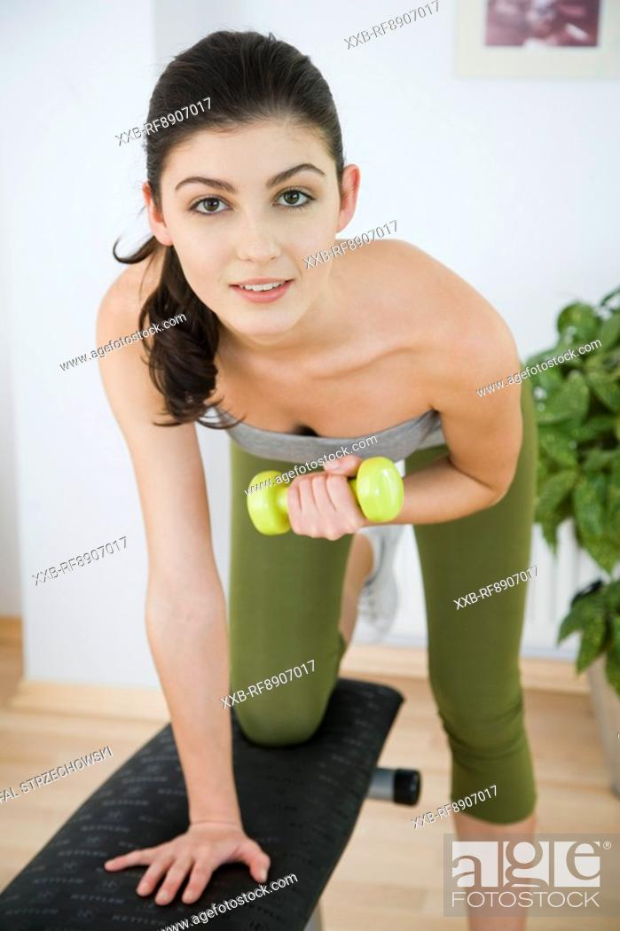 Stock Photo: young woman training with dumbbells.