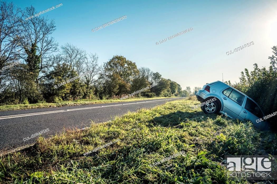 Stock Photo: Car sticking out of hedge on rural highway roadside.