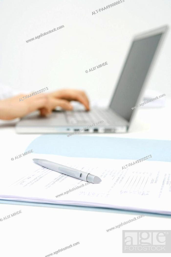 Stock Photo: Person using laptop computer, cropped view, focus on pen and document in foreground.