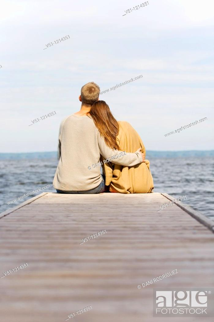 Stock Photo: Back view of a young couple sitting in a pier.