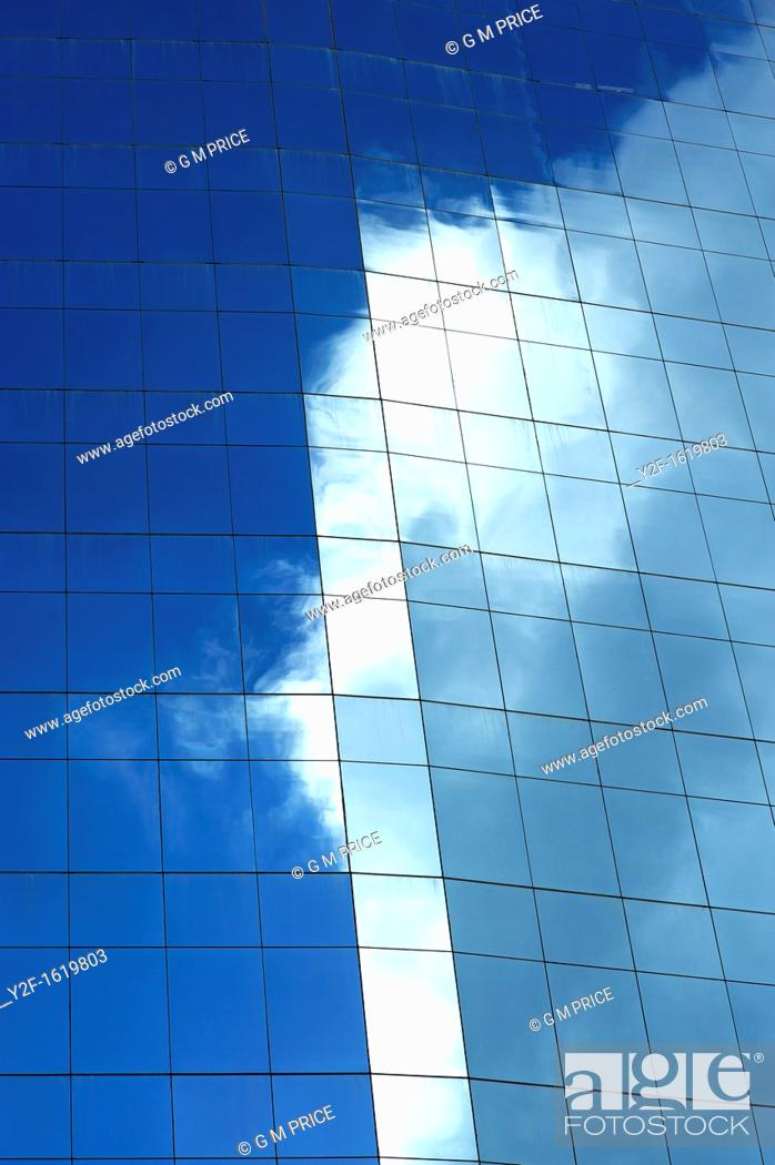 Stock Photo: cloud reflected in office building window.